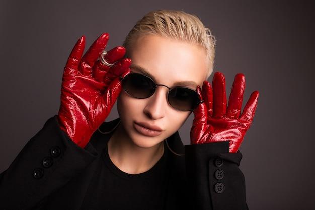 Portrait d'une blonde élégante avec des gants en cuir rouge