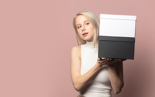 Portrait de blonde en haut avec des coffrets cadeaux noir et blanc sur rose