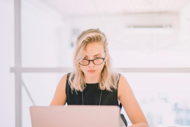 Portrait de blonde jeune femme regardant un ordinateur portable