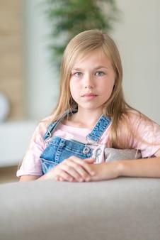 Portrait de blonde pré adolescente assise sur un canapé