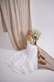Portrait d'une blonde sexy dans une belle robe blanche près d'un vase de fleurs sauvages. fille romantique avec un beau maquillage naturel