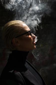 Portrait d'une blonde sexy qui fume et libère de la fumée