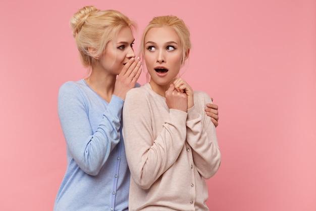 Portrait de blondes jumeaux mignons. la fille raconte à sa sœur la nouvelle de son ex-petit ami, dont elle est choquée, le second a ouvert la bouche de surprise, se tient sur fond rose.