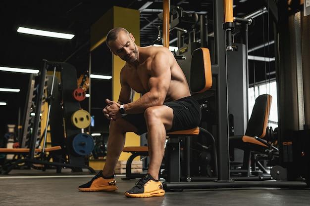 Portrait de bodybuilder beau et musclé dans une salle de sport pendant l'entraînement