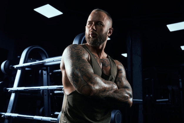 Portrait de bodybuilder masculin tendu en tenue de sport s'appuyant sur le support.