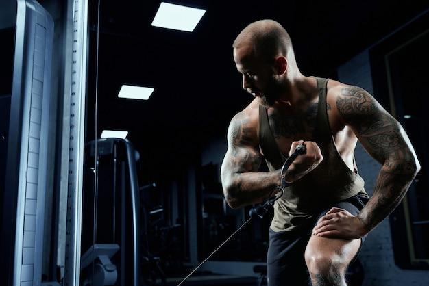 Portrait de bodybuilder tatoué musclé faisant des exercices croisés.