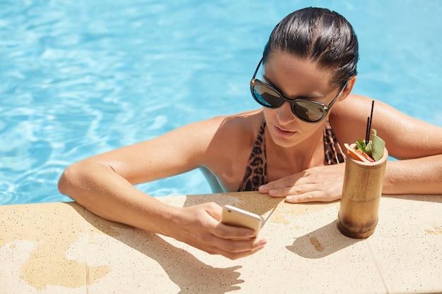 Portrait de bonne brune occupée à rester dans la piscine, tenant son smartphone dans une main, en tapant des messages