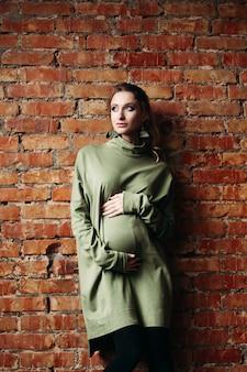 Portrait de bonne fille brune enceinte posant contre le mur de briques.