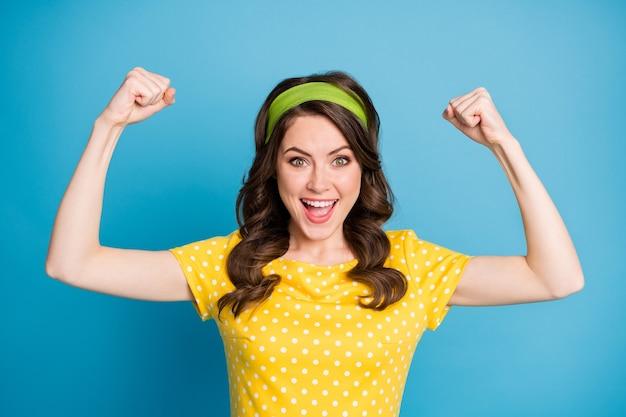 Portrait de bonne humeur fille énergique montre ses mains biceps isolées sur fond de couleur bleu