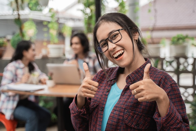 Portrait de bonne humeur de jeunes étudiants asiatiques montrant les pouces vers le haut de réunion dans un café