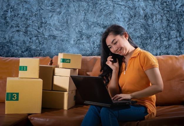 Portrait bored asia jeune femme est assise sur le canapé dans sa chambre les femmes ont utilisé un téléphone portable