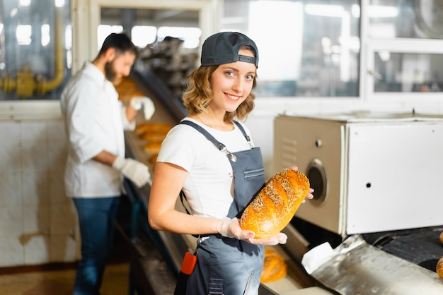 Portrait, boulanger, femme, pain, mains, contre, automatisé, ligne, boulangerie