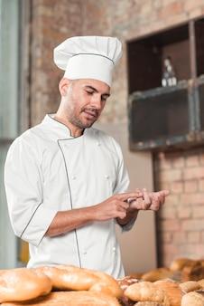 Portrait de boulanger mâle comptant des pains cuits au four