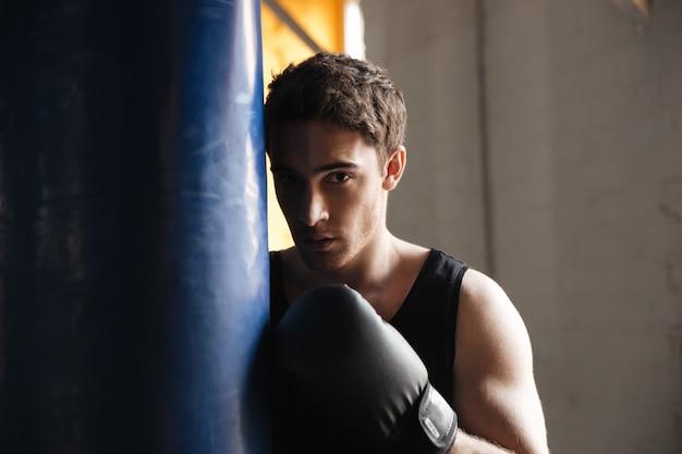 Portrait de boxeur près de punchbag dans l'ombre