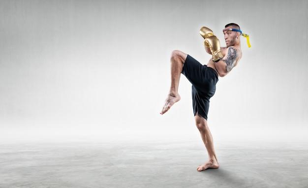 Portrait d'un boxeur thaïlandais. il frappe avec son genou. concept de compétitions et de tournois. technique mixte