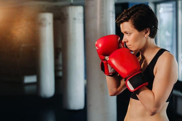Portrait d'une boxeuse en gants rouges dans la salle de sport pendant l'entraînement