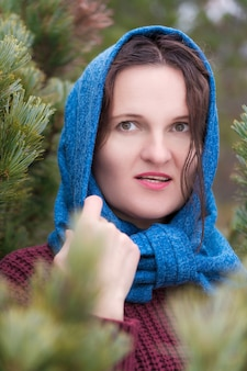Portrait de brune debout dans la forêt de pins. femme vêtue d'un pull marron, foulard bleu jeté sur la tête