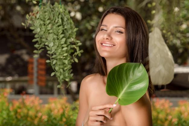 Portrait de brune souriante avec feuille verte, soin de la peau ou cosmétique bio