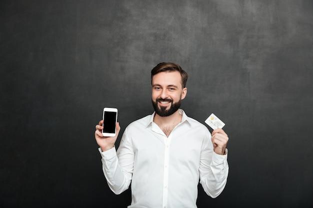 Portrait, de, brunette, homme, poser, appareil-photo, utilisation, smartphone, et, carte de débit, pour, achats en ligne, isolé, sur, gris foncé