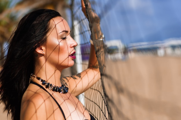 Portrait de brunette sexy avec des yeux fermés restant à côté du filet