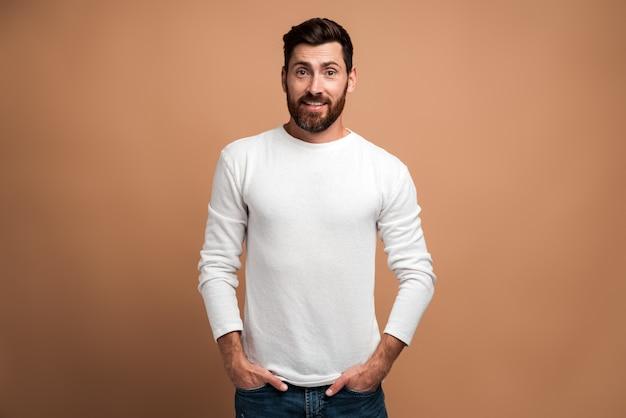 Portrait de brutal beau modèle de jeune homme barbu en chemise blanche debout et regardant la caméra avec plaisir visage fier. studio intérieur tourné isolé sur fond beige