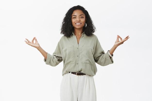 Portrait de calme, heureux et ravi, formateur de yoga féminin à la peau sombre détendue tenant la main dans la propagation zen