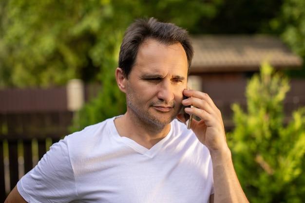Portrait calme d'homme d'affaires européen non rasé positif des années 40 en t-shirt blanc parlant sur téléphone mobile en plein air sur la nature verte floue. concept d'entreprise pour contrôler les sentiments