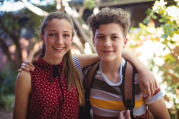 Portrait de camarades de classe heureux debout avec les bras autour