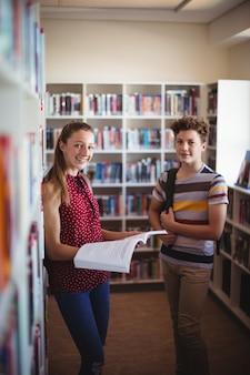 Portrait de camarades de classe heureux debout dans la bibliothèque
