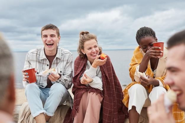 Portrait candide de jeune femme riant joyeusement tout en profitant du camping sur la plage en automne avec di...
