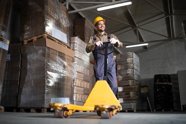 Portrait de caucasien souriant travailleur d'entrepôt debout par chariot élévateur manuel dans la salle de stockage.