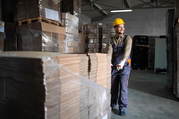 Portrait de caucasien souriant travailleur d'entrepôt tirant la charge et les palettes sur chariot élévateur manuel dans la salle de stockage.
