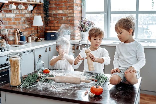 Portrait chaleureux d'une bonne relation de frères. trois enfants d'âge préscolaire s'amusent et apprennent à cuisiner dans une cuisine moderne.