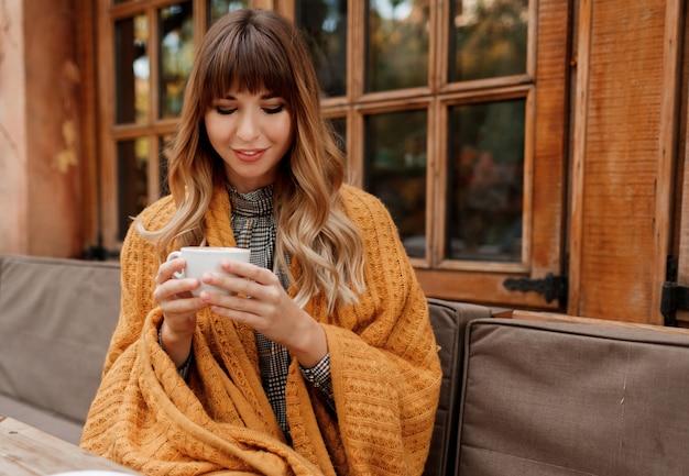 Portrait chaleureux et confortable d'une femme rêveuse heureuse avec des cheveux ondulés, recouvert de plaid jaune et tenant une tasse de cappuccino chaud. femelle blanche se détendre sur la terrasse.