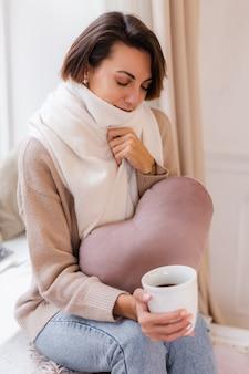 Portrait chaleureux de femme assise sur le rebord de la fenêtre avec une tasse de café thé chaud portant chandail et foulard blanc