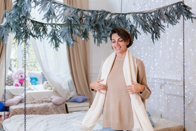 Portrait chaleureux de femme heureuse en pull, jeans et écharpe blanche à la maison dans la chambre