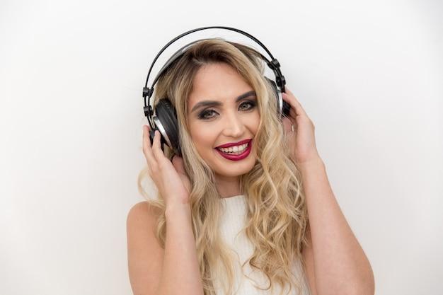 Portrait d'un chanteur de jeune femme avec un casque. écouter de la musique.