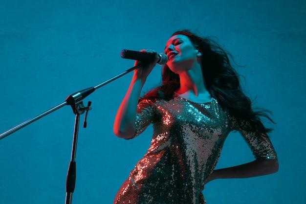 Portrait de chanteuse caucasienne isolé sur fond bleu studio en néon