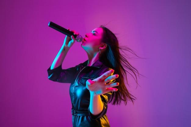 Portrait de chanteuse caucasienne isolé sur fond de studio violet en néon. beau modèle féminin en tenue noire avec microphone. concept d'émotions humaines, expression faciale, publicité, musique, art.