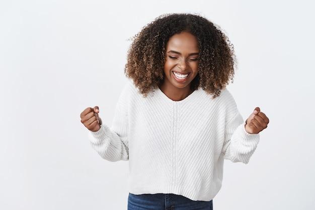 Portrait charmant afro-américain souriant femme heureuse serrer les poings victoire geste triomphant effectuer succès mouvement de danse célébrer la bonne nouvelle, mur blanc