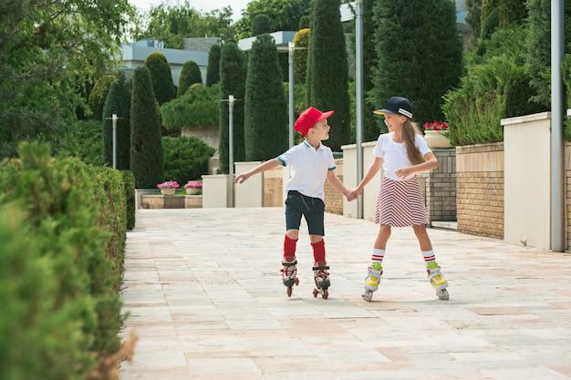 Portrait d'un charmant couple d'adolescents faisant du patin à roulettes ensemble