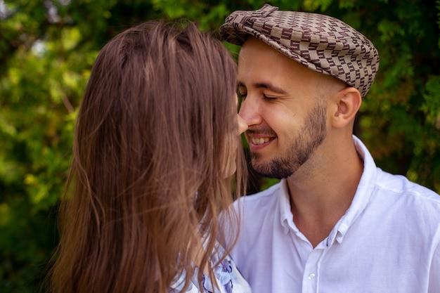Portrait d'un charmant couple amoureux touche leur nez et sourit dans le jardin verdoyant