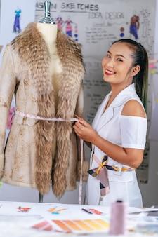 Portrait charmant créateur de mode asiatique ou sur mesure sourire féminin avec heureux dans un atelier moderne