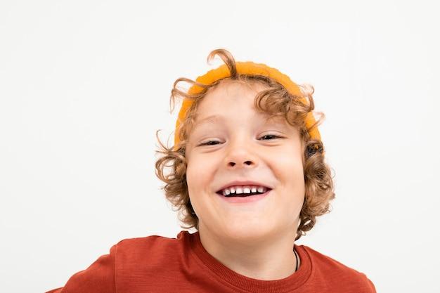 Portrait de charmant garçon aux cheveux bouclés, chapeau jaune sourit isolé sur blanc