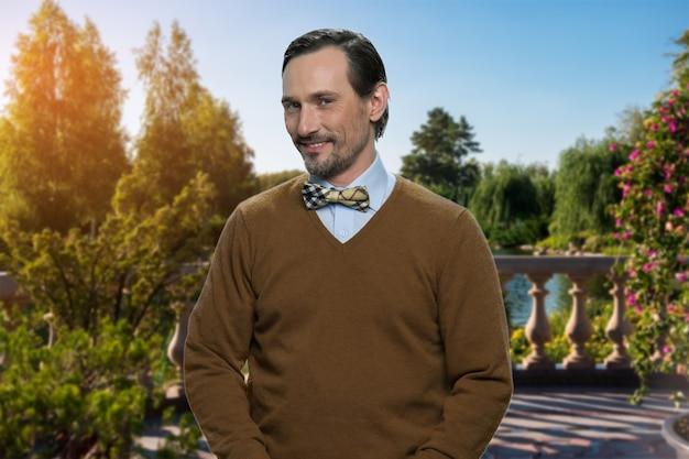 Portrait de charmant homme mûr debout dans le parc. bel homme d'âge moyen souriant à l'extérieur.