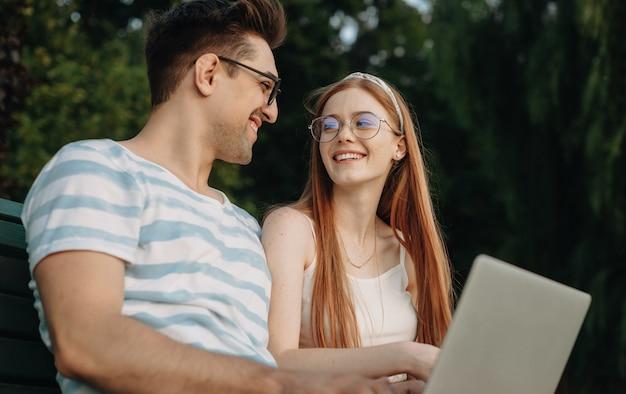Portrait d'un charmant jeune couple à la recherche de l'autre en riant tandis que l'homme tient un ordinateur portable sur ses jambes à la pige en plein air dans le parc sur un banc.