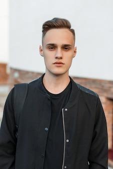 Portrait d'un charmant jeune homme avec une coiffure élégante dans une veste d'été noire dans un t-shirt élégant avec un sac à dos noir