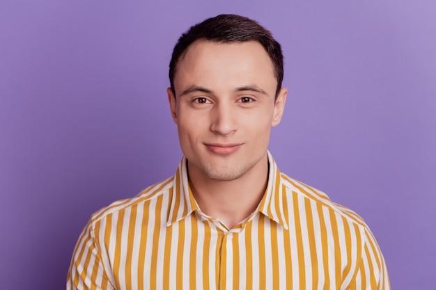 Portrait de charmant mec séduisant look caméra sur fond violet