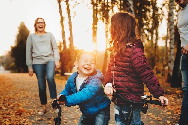 Portrait d'un charmant petit frère et soeur riant assis sur leurs vélos dans le parc contre le coucher du soleil avec leurs parents.