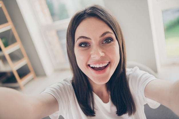 Portrait de charmante adolescente mignonne faisant selfie à pleines dents souriant chaise assise dans la maison à l'intérieur